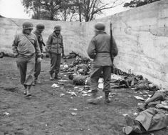 Officers of the US 42nd Infantry Division view the bodies of SS guards executed by their troops at the Dachau concentration camp upon liberation in April 1945. The incident attracted senior command attention but no penalties were imposed on those who participated in the shooting.