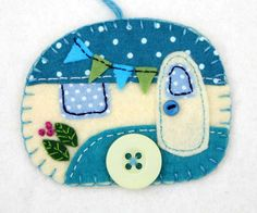 Vintage caravan trailer ornament, handmade from felt and decorated with fabric scraps. With tiny felt bunting and buttons for the wheel and door knob. Colors are teal and cream. With blanket stitched