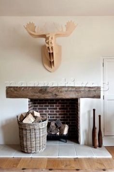 Carved Wooden Stags Head Mounted Above Exposed Brick Fireplace With Log Basket In Canterbury Home E