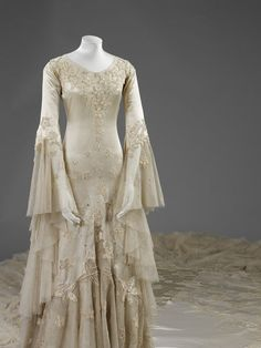 Wedding dress: Date:1933 (made) Artist/Maker:Hartnell, Norman, born 1901 - died 1979 (designer) Materials and Techniques:Embroidered silk satin with pearl and glass beads and satin appliqué, tulle with metal wire, trimmed with wax. Detail