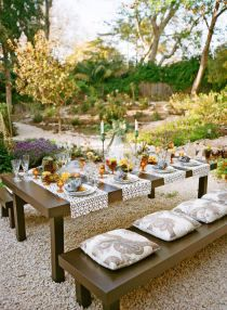 Chunky wood outdoor dining table and benches softened with pillows