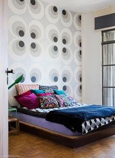 Quarto com papel de parede com estampa anos 70 e muitas almofadas coloridas e estampadas.
