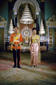 Formal portrait of Thailand's King Bhumibol Adulyadej (aka Phumiphon Aduldet) and Queen Sirikit at the Palace in 1960. The nine-tiered parasol in background is a symbol of the Chakri Dynasty.