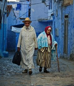 Elderly couple in Chefchaouen wearing traditional Moroccan clothes.