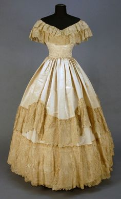 1855-1860 moire wedding gown: 2-piece ivory faille having boned boatneck bodice with double lace neckline ruffle over cap sleeve, full skirt decorated with lace swags, and deep lace hem band.