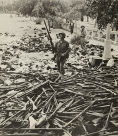 American M.P. standing on a large pile of Italian weapons on a street in Palermo, Italy, on August 6, 1943. Palermo, a strategic port, fell on July 20, only 10 days after the Allied invasion of Sicily.