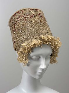 Headdress (kokoshnik) About 1820 DIMENSIONS 24.1 x 16.2 x 16.2 cm (9 1/2 x 6 3/8 x 6 3/8 in.) MEDIUM OR TECHNIQUE Silk velvet embroidered with metallic yarns, spangles, and colored glass; trimmed with gold gimp and glass beads Red velvet heavily covered with embroidery, done with gold and silver thread, spangles and colored glass jewels.   Province of Moscow about 1820.