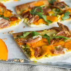 Herbst-Flammkuchen: Dünner Teig wird mit Crème fraîche bestrichen, mit Schinken und süßem Kürbis belegt, im Ofen knusprig gebacken und mit Ruccola getoppt.