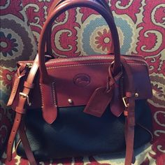 Dooney and Bourke Bag Beautiful Bkack and Tan Donney   10.5\14 wide has shoulder strap that is 35 inches long but can be shortened or lengthened.  I side has three drop in pockets and one zip picket plus a key fob. Great bag  for any season. No spots, tears or smells  Dooney & Bourke Bags Satchels