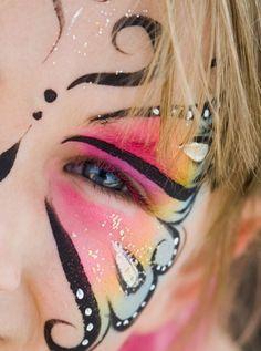 Nahaufnahme eines Mädchengesichts mit bunter Schmetterling-Gesichtsbemalung