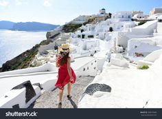 Santorini Travel Tourist Woman On Vacation In Oia Walking On Stairs. Person In Red Dress Visiting The Famous White Village With…