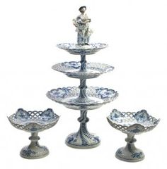 A Collection of Meissen Porcelain Articles,  in the Blue Onion pattern, comprising a reticulated three tier figural tazza, two reticulated tazze, two reticulated square dishes and others; 9 items total.  Height of tallest 21 1/2 inches.