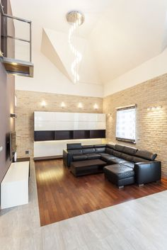 Living room defined by dark hardwood flooring wrapped in grey marble, this minimalist space stands white and dark wood cabinetry next to beige brick walls, with large L-shaped black leather sectional at center. Spiral chandelier and small balcony overlook the space.