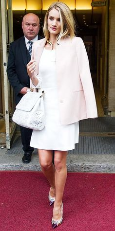 MAY 20, 2014  Rosey Huntington-Whiteley stepped out in Berlin wearing a LWD and statement accessories — including a leather-and-lace Dolce amp Gabbana bag. The model topped off her look by effortlessly draping a pastel pink blazer over her shoulders.