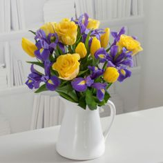 This Easter inspired jug contains a mix of blue iris, yellow roses and tulips