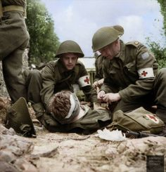 Major John W. Forth, Chaplain of The Cameron Highlanders of Ottawa (right), Canadian 3rd Infantry Division, helping the unit's Regimental Aid Party treat a wounded comrade during the Battle of Caen, France, 15 July 1944.