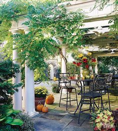 Architectural elements can transform an ordinary outdoor structure into something extraordinary. This pergola has classic rounded columns and beautifully detailed crossbeams that pick up on architectural details from the house. Underlaid with slate pavers and wired with ceiling fans, it's the perfect spot for a meal--morning, noon, or night./