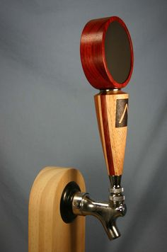 Chalkboard beer tap handle with Padauk top, and African Mahogany base with Maple and Padauk stripes. A simple logo was burned by hand for the customer - Please contact me to discuss your logo. The finish is several coats of Danish oil. The colors are all natural - no stains or dyes are used.   The painted chalkboard insert is carefully sized to fit snugly in the recessed top. The base, top, and chalkboard are all permanently attached. There is a nickel-plated collar between the top and the…