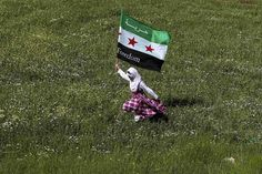 A Syrian refugee runs with a Syrian opposition flag during a demonstration against Syria's President Bashar al-Assad, outside the Syrian embassy in Amman.