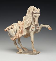 A PAINTED POTTERY FIGURE OF A PRANCING HORSE -  TANG DYNASTY (618-907)