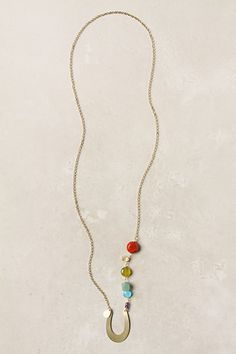 """This rainbow of winking gems leads to a horseshoe so lucky, you won't miss the pot of gold. 12k gold plated brass, sponge coral, citrine, quartz, avanturine, amethyst, brass  28.5""""L  1.5"""" pendant  Handmade in USA"""