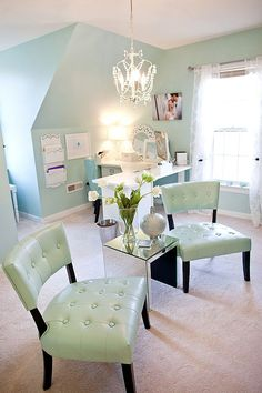 This sweet room focuses on a light and airy ambiance with a sparkling chandelier and light mint walls, chairs, and decor.