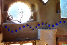 The Cob project - A cob house with round window & glass bottles in the walls