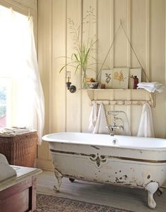 Simple wood trim adds architectural detail to the wall and a wire coat rack serves perfectly to hang towels by the clawfoot bathtub