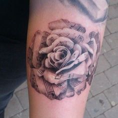 This gorgeous rose tattoo appears as if it is made of sheet music
