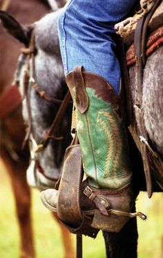 """Working boot in the stirrup with a small rowel spur. Spur rowels look """"meaner"""" than they are, as the rotation tempers the touch on the horse. Spurs are worn sitting on the spur rest of the boot, with the buckle of the spur strap worn around the top of the foot. Some cowboys also added small metal Jingo Bobs or Jingle Bobs, (Pajados) near the rowel to create a jingling sound whenever the foot is moved."""