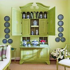 A tall secretary cabinet is painted in a slightly zingier green than the walls, while the blue china and plates help to bring contrast in this entry. Source