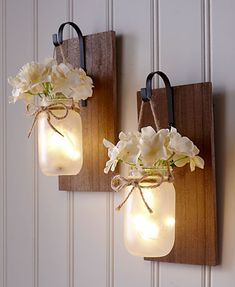 This Hanging Mason Jar Sconce has a natural look that spruces up any room. It comes with faux hydrangeas that are removable. The inside of the jar is filled wit