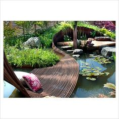 Pond garden with centrepiece ribbon of woven rebar steel, deck area for sitting, wildflower meadow mat of native plants, green roof and wooden screen fencing