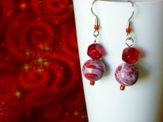 The red and white beads were handpainted, but look like marble. Drops 1 inch from bottom of ear wire. the little square bead is deep red glass.