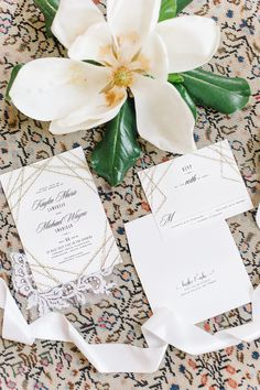 Wedding invitations staged with Magnolia Flower.  Wedding Planner | Mac & B Events >> Photography | Aaron and Jillian Photography
