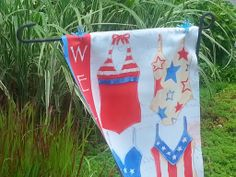 Use plant clips to keep your garden flag from sliding off the holder when its windy. Clips still let the flag move back and forth. These are dragonfly clips, but any would work.