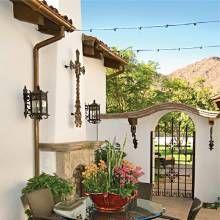 Strung lights crisscross a Spanish-style patio via Phoenix Home & Garden