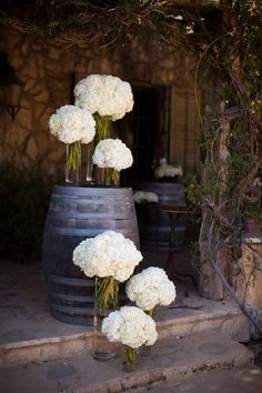 Love the staggered flowers, good for entrance. VH  vineyard wedding: barrels and hydrangeas