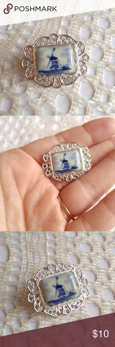 Vintage Delft windmill brooch silver tone This pretty little vintage brooch has a porcelain center that is painted with a Delft style blue windmill scene! It is in an ornate silver tone metal setting with a c clasp closure. This brooch is in great shape and from a smoke free home :)    FOXE8188DELFT888 Vintage Jewelry Brooches