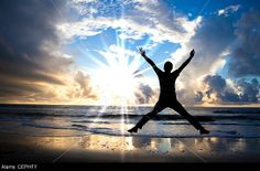 happy man jumping on the beach with beautiful sunrise © Tom Wang / Alamy