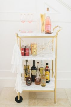 To make over your utility cart into a glam bar cart like this one, spray the metal furnishings with gold paint + cover the surfaces with marble contact paper.