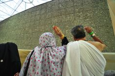 A man and woman perform the ritual of throwing stones to signify when the Prophet Ibrahim threw stones at Satan