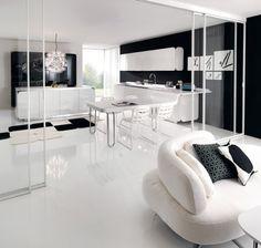 Cocina en blanco y negro, abierta al salón, con pared de cristal