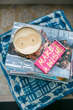 Pouf as coffee table with candle and magazines