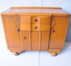 An Art Deco English oak sideboard. The mid section has two drawers over a single door. The two outer doors enclose shelving and are decorated with geometric  flower carving and have wooden knobs. Raised on bolbous feet.