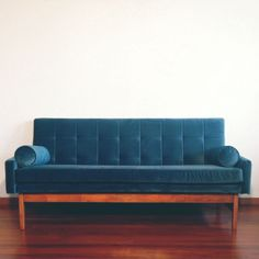 """An iconic Fred Lowen design mid-century sofa.""""Captain Peacock"""" has been fully refurbished from top to toe. The wooden base has been lovingly restored using traditional methods, protected in 5 coats of shellac and wax. Luxurious new high-grade foam has been upholstered in Warwick Fabric's stunning peacock blue """"Mystere"""" velvet.  Classic mid-century features include tufted backrest detailing, top-stitched arms and backrest and piped cushion edges. The singl..."""