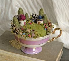 fairies must live in this magical little land. Tiny houses, trees, mushrooms and gardens are nestled into this sweet antique teacup