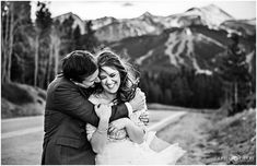 Bride and groom cuddle to stay warm outside during their wedding day portraits with the Breckenridge mountains as the backdrop in Colorado. - April O'Hare Photography http://www.apriloharephotography.com