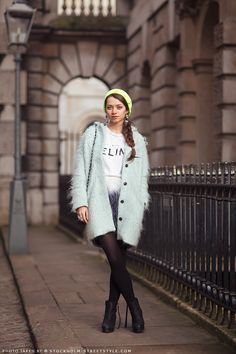 Alina in a CELINE t-shirt, feathered skirt, pale blue mohair coat, and black ankle boots.