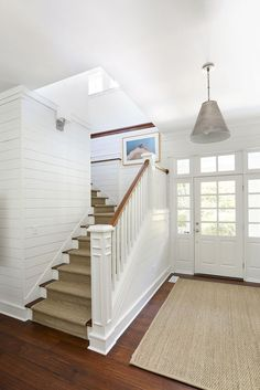 This bright, well proportioned hallway shows just how you can have great Hamptons style without the soaring double-height space - dark wooden floors and white painted wood panelling are key elements